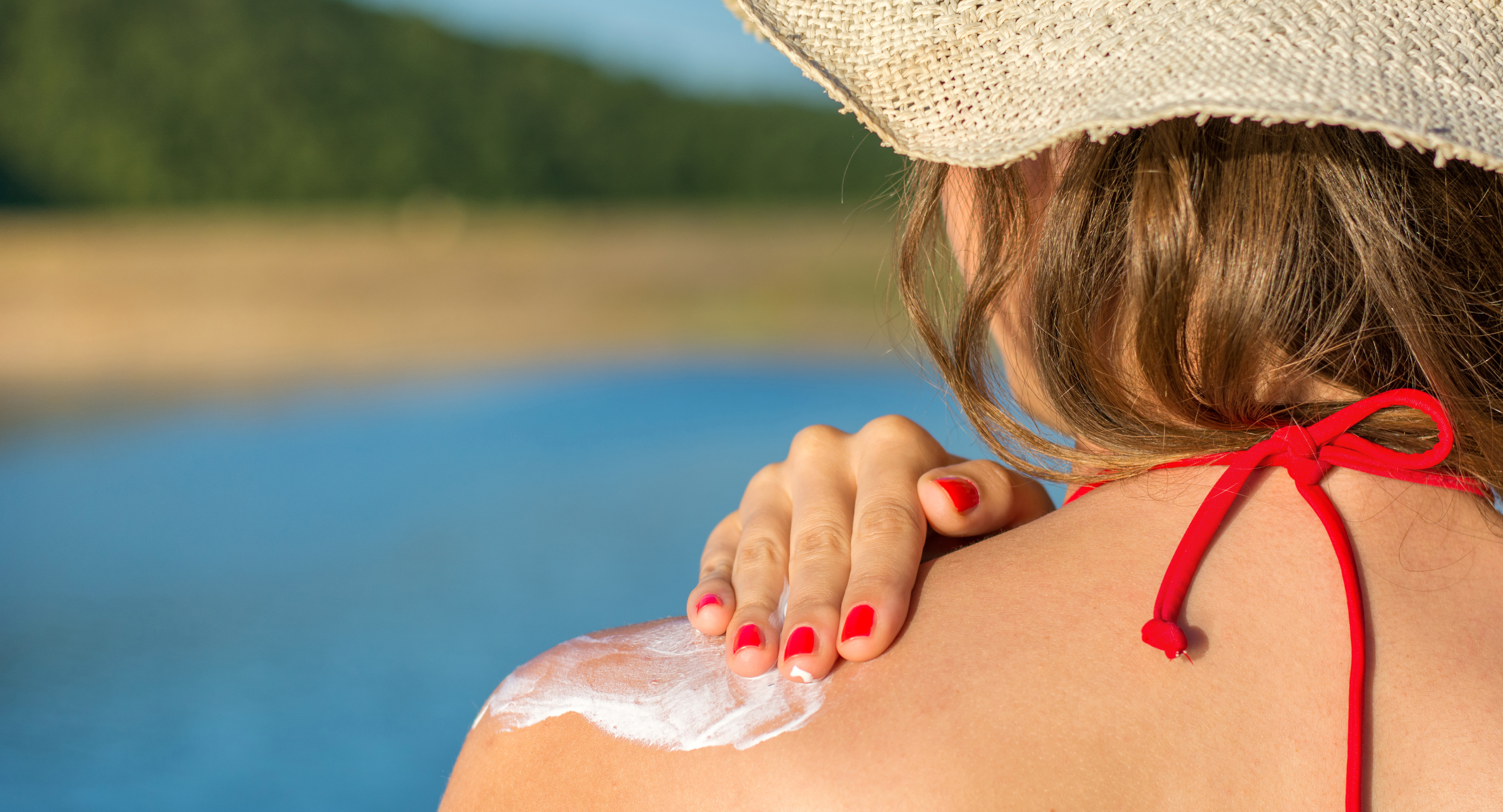 Young woman applying sun lotion on summer vacation