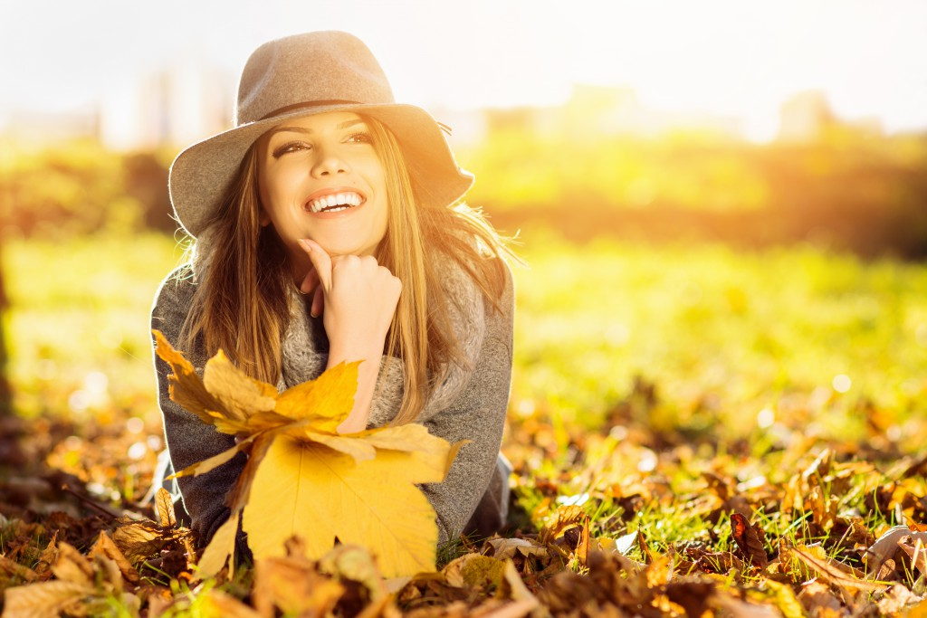 Happy young woman in park on sunny autumn day